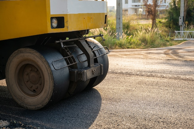 Yellow steamroller or soil compactor working on asphalt highway road at construction site