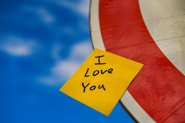Yellow stick with the inscription i love you on a road sign in the sky.