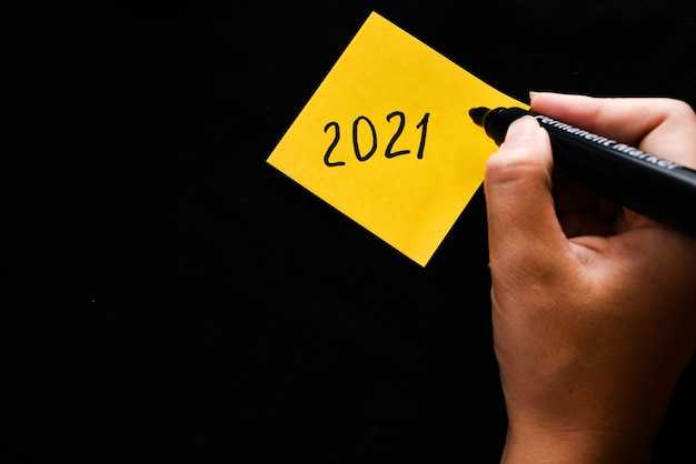 Yellow sticker with the symbol 2021 and a hand holds a marker.