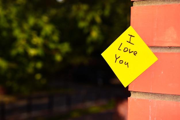 Желтая наклейка с надписью i love you приклеена к кирпичной стене