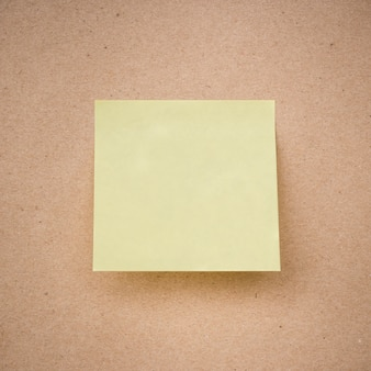 Yellow sticky note on brown paper texture close up