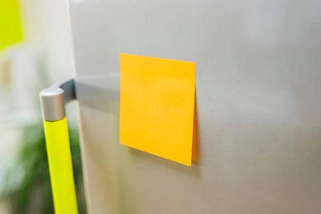Желтая записная книжка на холодильнике