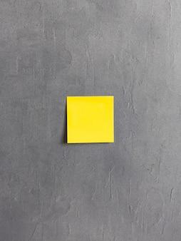 灰色のセメントの背景に黄色の付箋。高品質の写真