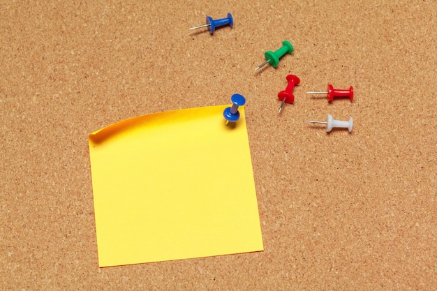 Yellow sticky note with pushpins on cork surface