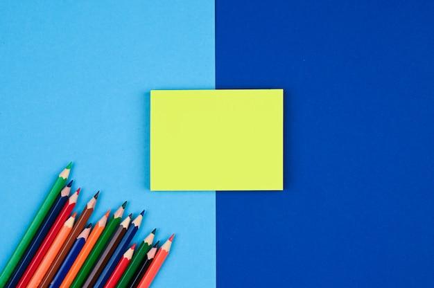 黄色の付箋と青い表面に色鉛筆