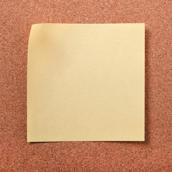 Yellow sticky post note on cork board