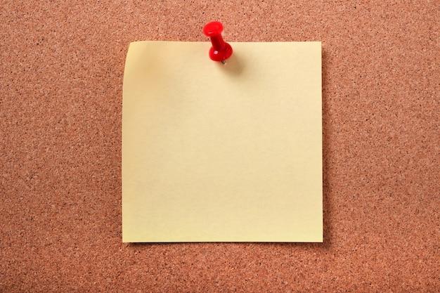 黄色の粘着性のポストノートはコルク板を固定