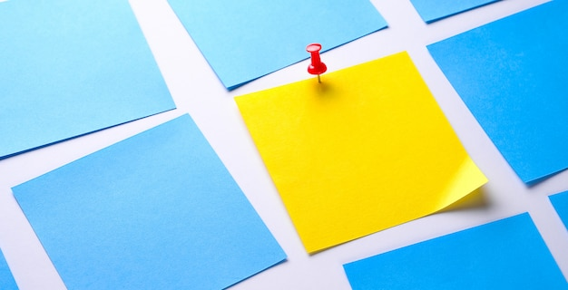 Yellow sticky sticker on a white background for reminding information, attached with a paper clip. space for text. there are empty blue stickers next to it. banner.