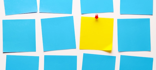 Yellow sticky sticker on a white background for reminding information, attached with a paper clip. space for text. there are empty blue stickers next to it