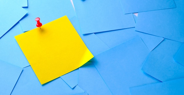 Yellow sticky sticker on a white background for reminding information, attached with a paper clip.