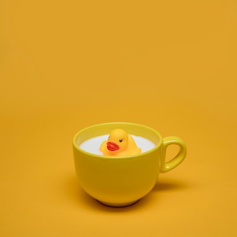 Желтый натюрморт ванны утки в чашке молока