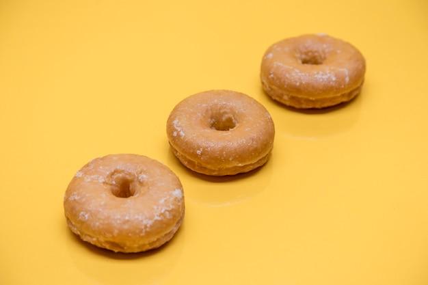 Yellow still life of three donuts