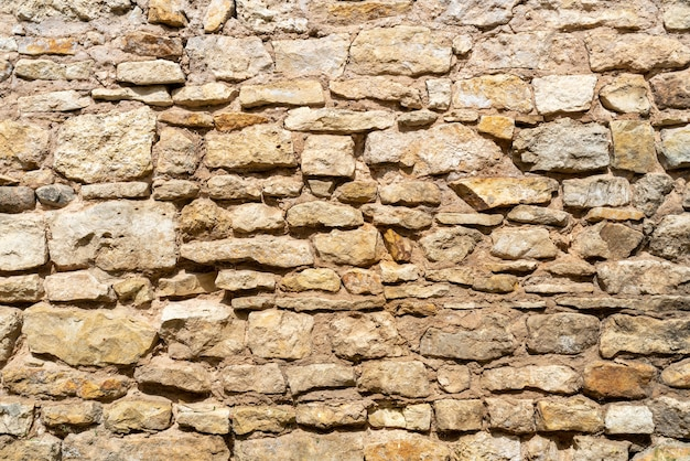 Желтая каменная стена. текстура каменной стены старого дома.