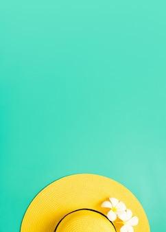 햇빛이 비치는 흰색 플루메리아 꽃 배경이 있는 녹색 청록색 위에 노란색 밀짚 모자, 최소한의 여름 해변 바다, 수직