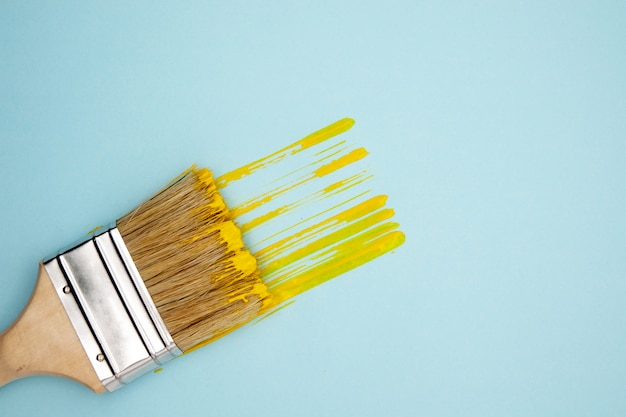 Yellow streak of paint and brush on blue background