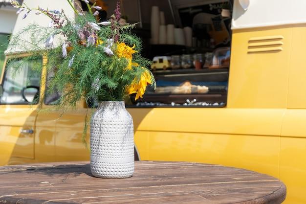 花とテーブルの近くの車輪の上の黄色いストリートコーヒーショップ。晴れた日に空のラウンドテーブルとヴィンテージフードトラック。