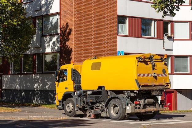 Желтая подметально-уборочная машина на работе