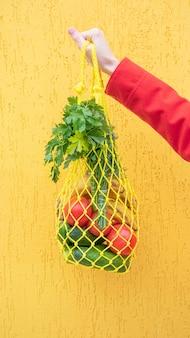 손 클로즈업에 오이, 토마토, 바나나, 허브가 든 노란색 끈 가방. 빨강, 노랑, 녹색 톤의 밝은 사진. 지속 가능성, 폐기물 제로, 플라스틱 없는 개념, 채식주의, 건강 식품.