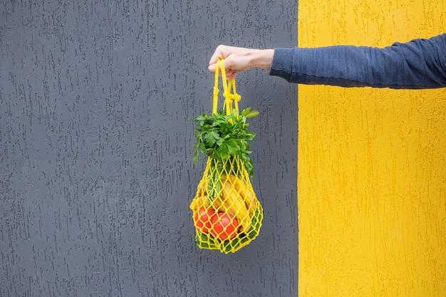 Желтая авоська с огурцами, помидорами, бананами и зеленью в руке крупным планом. яркое фото в красных, желтых, зеленых тонах. экологичность, нулевые отходы, концепция без пластика, вегетарианство, здоровое питание.