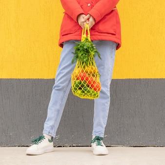 청바지, 빨간 재킷을 입은 소녀의 손에 오이, 토마토, 바나나, 허브가 든 노란색 끈 가방. 빨간색, 노란색 및 녹색 톤의 밝은 사진. 지속 가능성, 폐기물 제로, 플라스틱 없는 개념.