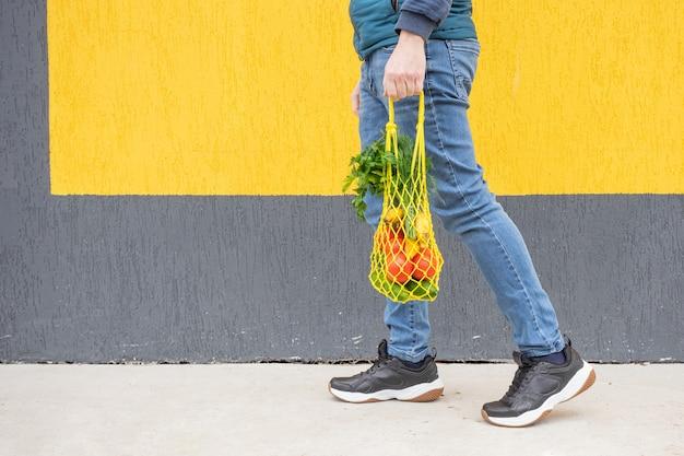 청바지를 입은 남자의 손에 오이, 토마토, 바나나, 허브가 든 노란색 끈 가방. 빨간색, 노란색 및 녹색 톤의 밝은 사진. 지속 가능성, 폐기물 제로, 플라스틱 없는 개념.