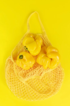 Yellow string bag with yellow fresh peppers. eco bio products, ugly natural foods, healthy, dietary and vegetarian foods