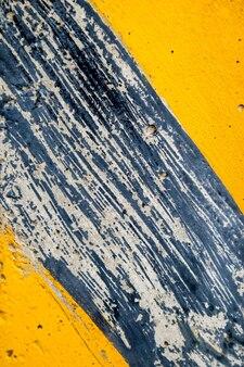 Yellow striped road markings on black asphalt