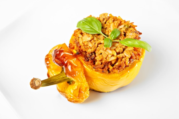 A yellow stuffed pepper baked and served on a white plate