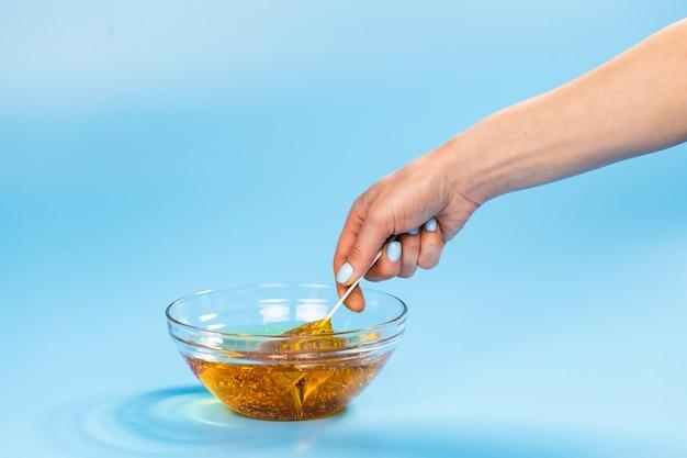 Желтая сахарная паста для шугаринга на шпателе крупным планом на синем фоне. косметология и
