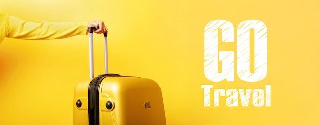 Yellow suitcase in hand and inscription go travel over yellow wall, travel concept,