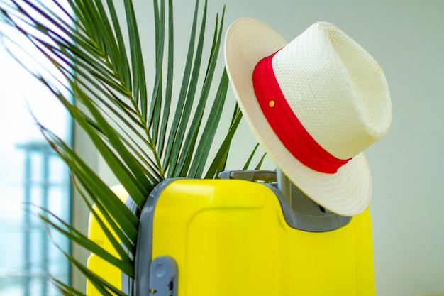 Yellow suitcase, hat and palm branch for a vacation trip