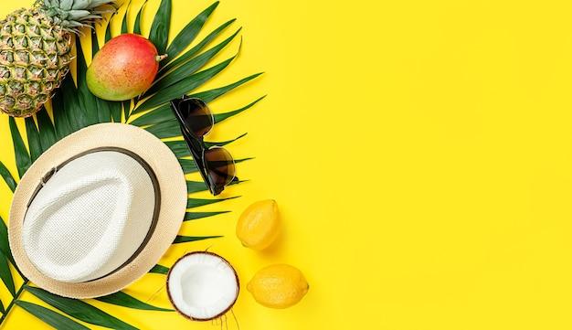 Желтый летний фон из тропических фруктов, шляпы и солнцезащитных очков. накладные расходы, скопируйте пространство.