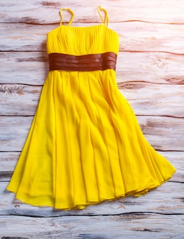 Желтое летнее платье. желтое платье на деревянных фоне. женская одежда для теплого времени года. стильный предмет одежды.