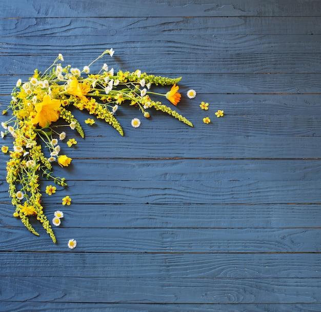 青い木製の背景に黄色の夏の花