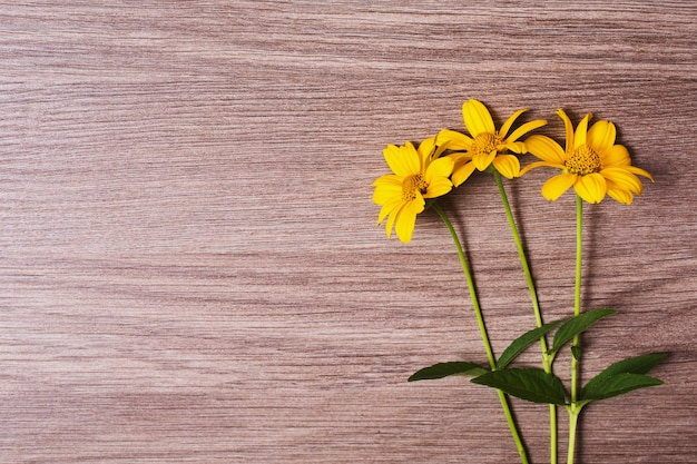 Yellow summer flowers on a wooden background. bright floral composition. space for text. green stalks on a brown table. template for greeting card.
