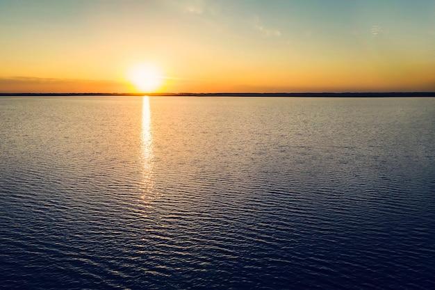 За озером садится желтое солнце. закат на берегу моря. красивый закат на озере. красивый восход солнца на озере. беречь природу. солнце садится ха горизонт