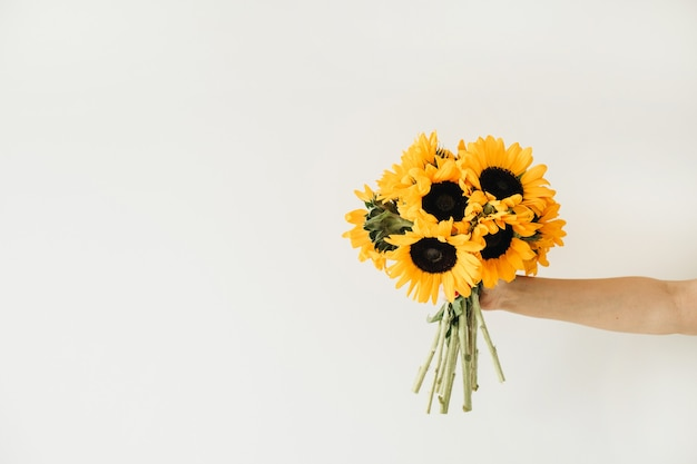 Букет желтых подсолнухов в женской руке на белом