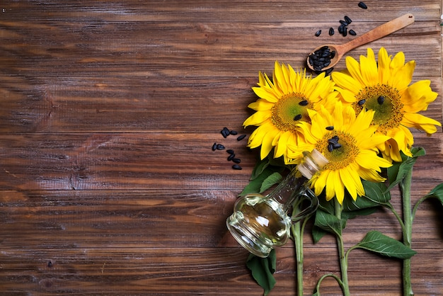Yellow sunflowers with oil glass bottle on background of old fence.