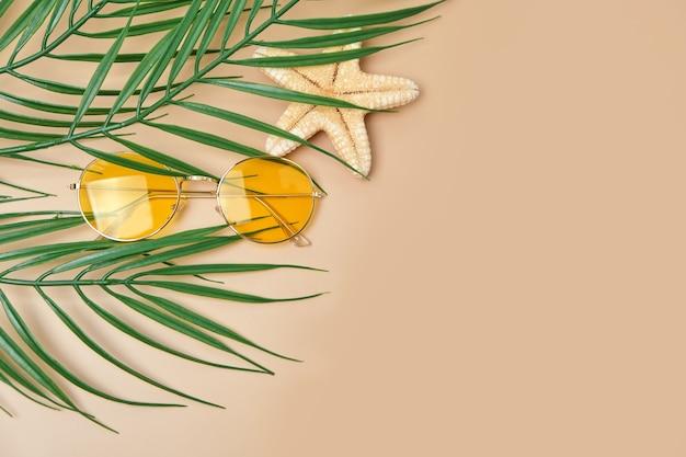 黄色のサングラスとヤシの葉はベージュの表面に上面図を残します