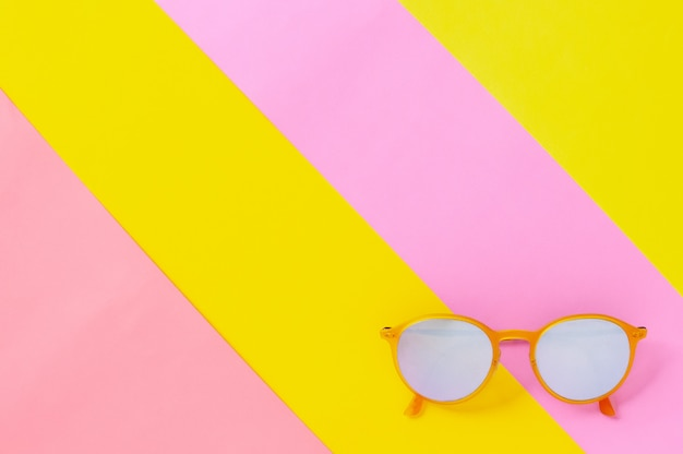 Yellow sunglasses isolated on colorful background.