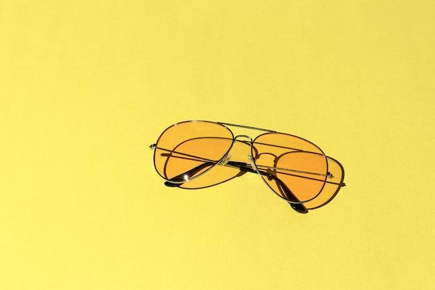 Желтые солнцезащитные очки, изолированные на ярком фоне. жесткие тени от солнца