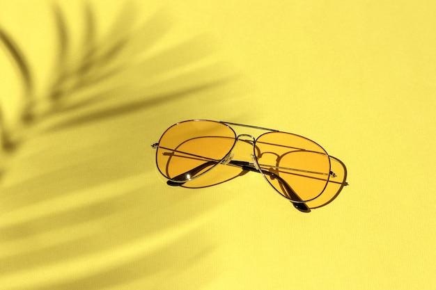 Желтые солнцезащитные очки на пастельном фоне под тенью пальмы. концепция досуга, путешествий и развлечений с копией пространства