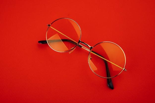 赤い背景に黄色のサングラス、夏、休暇のミニマルなコンセプト。