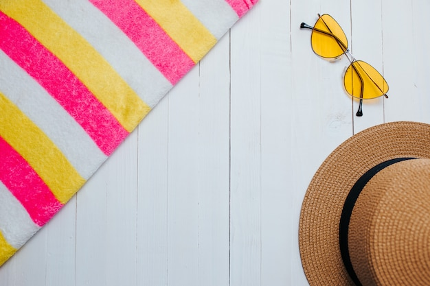 Yellow sunglasses and striped colorful towel on the white wood