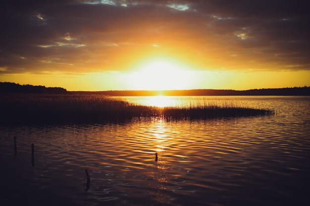 湖に沈む夕日。ぼやけた自然の背景、湖に沈む夕日。シルエットネイチャーバナー