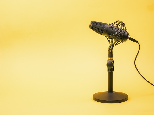 A yellow surface and a modern condenser microphone