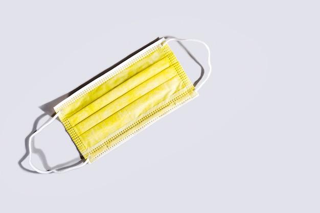 Желтая хирургическая маска для защиты лица, изолированные на сером столе. медицинская маска как часть средств защиты от вспышки вируса covid-19. модные цвета 2021 года.