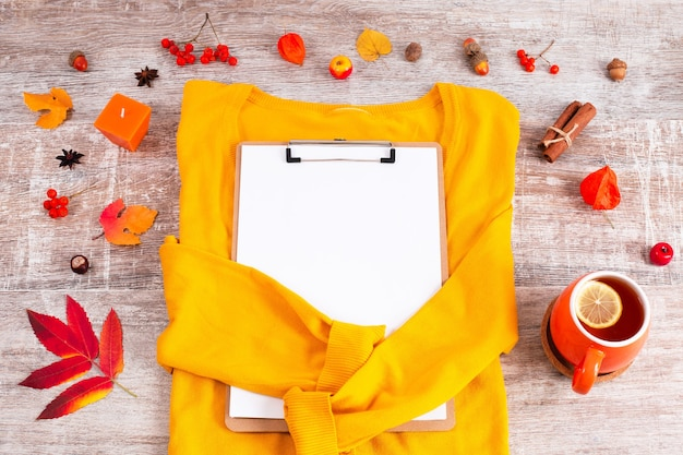 キャンドルドライリーフティーの周りにクリップボードと黄色のセーター