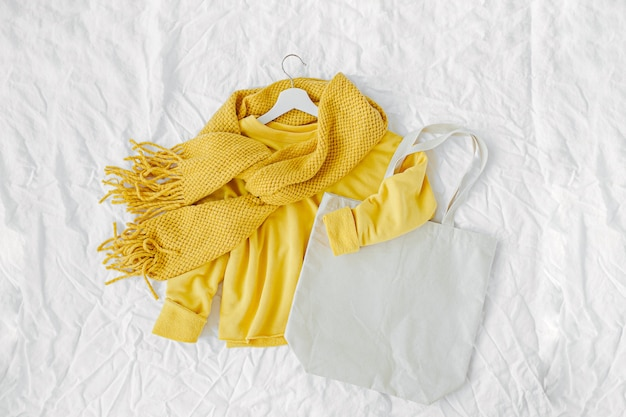 ニットスカーフとトートバッグが付いた黄色いセーター。白い背景の上の秋のファッションの服のコラージュ。上面図フラットレイ。