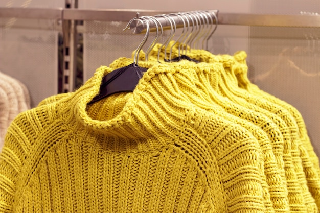 Yellow sweaters hanging on hangers in store, concept of clothing purchase